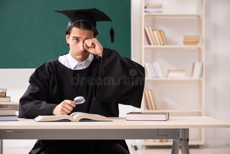 Der Student im Aufbaustudium vor gr?nem Brett lizenzfreies stockbild