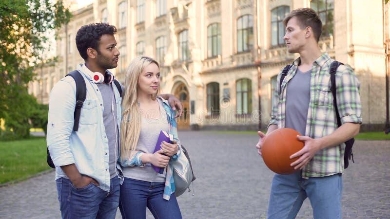 Der Student, der mit gemischtrassigen Paaren spricht, nähern sich College, sorglosem Studentenleben lizenzfreies stockbild