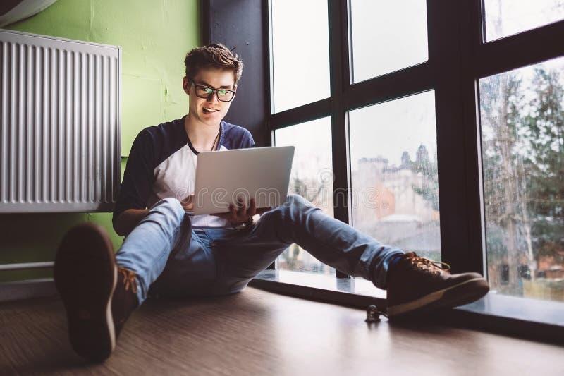 Der Student, der mit Laptop arbeitet, sitzt auf dem Boden nahe dem Fenster stockbild