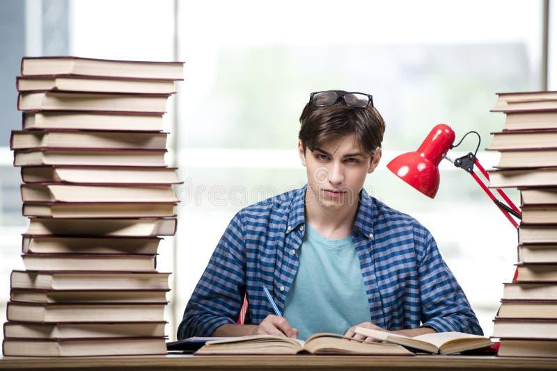 Der Student mit vielen Büchern, die für Prüfungen sich vorbereiten stockfotos