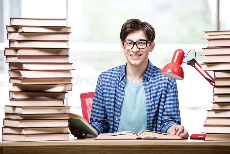 Der Student mit vielen Büchern, die für Prüfungen sich vorbereiten lizenzfreie stockfotografie