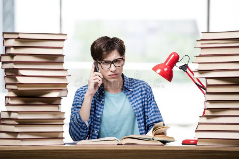 Der Student mit vielen Büchern, die für Prüfungen sich vorbereiten lizenzfreies stockfoto
