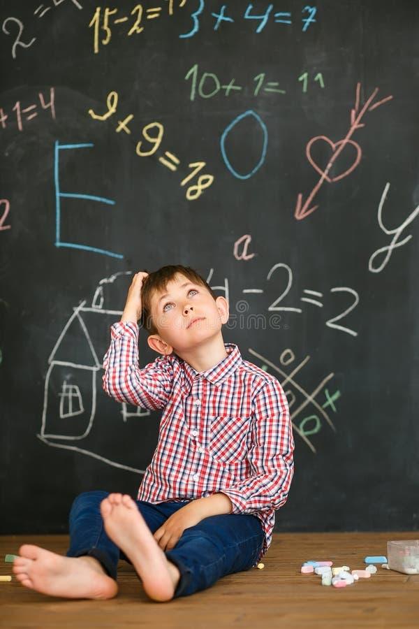 Der Student sitzt auf dem Hintergrund der Schulbehörde in der Rücksichtnahme über der Lösung des Problems lizenzfreie stockbilder