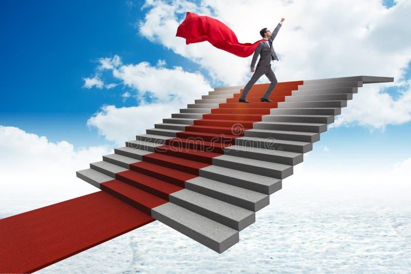 Der Superheldgeschäftsmann, der Treppe des roten Teppichs klettert lizenzfreie stockbilder