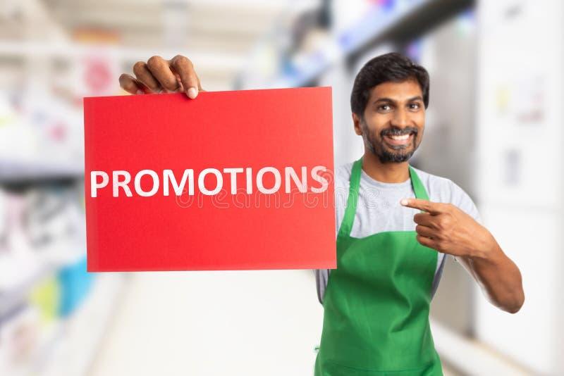 Der Supermarktangestellte, der Förderungen hält, simsen auf Papier lizenzfreie stockfotografie