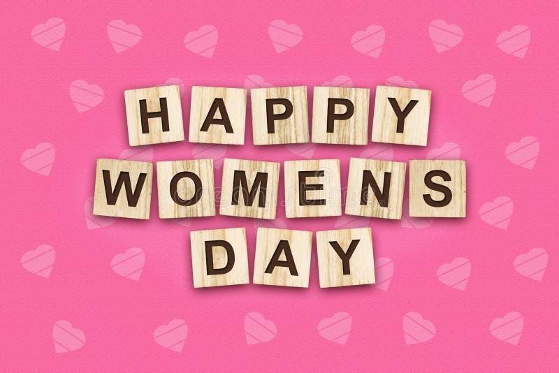 Der Tag der glücklichen Frauen, besteht die Aufschrift aus dem Alphabet auf hölzernen Würfeln Rosa Hintergrund lizenzfreies stockfoto