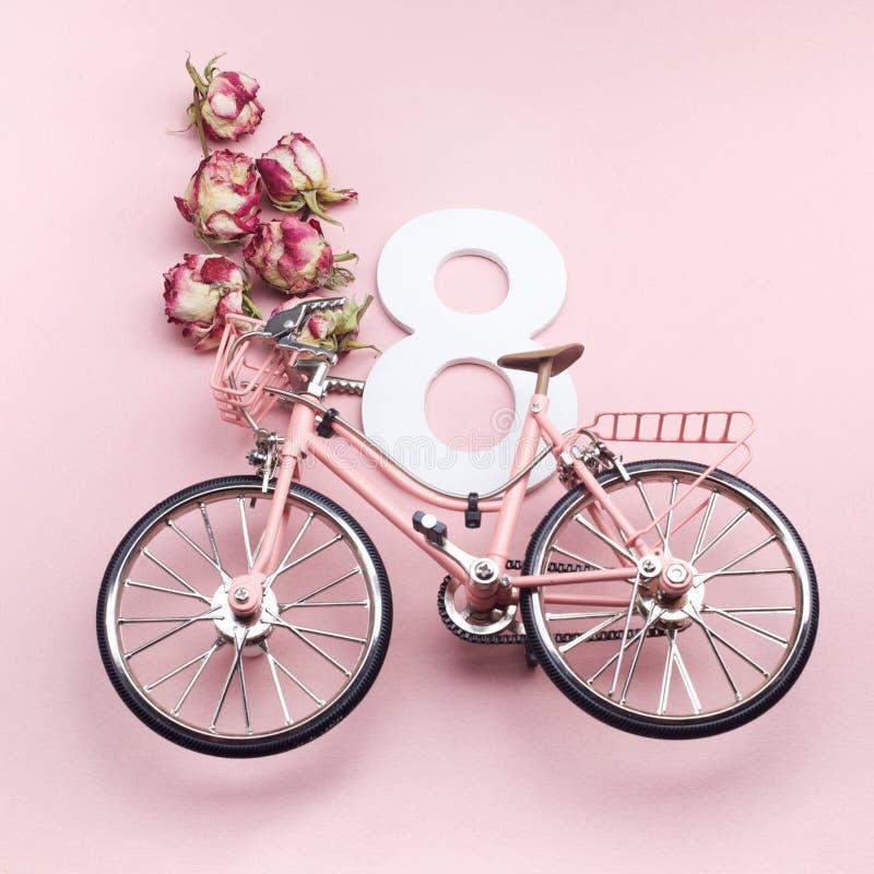 Der Tag der glücklichen internationalen Frauen feiern am acht März Nr. acht mit rosa Fahrrad auf rosa Hintergrund stockfotografie