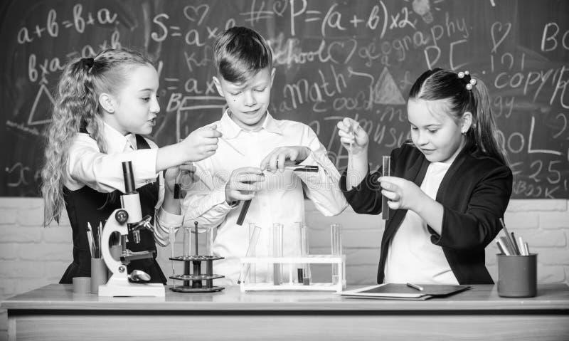 Der Tag der Kinder chemie Zur?ck zu Schule Studenten, die Biologieexperimente mit Mikroskop tun Kleinkindlernen stockbilder