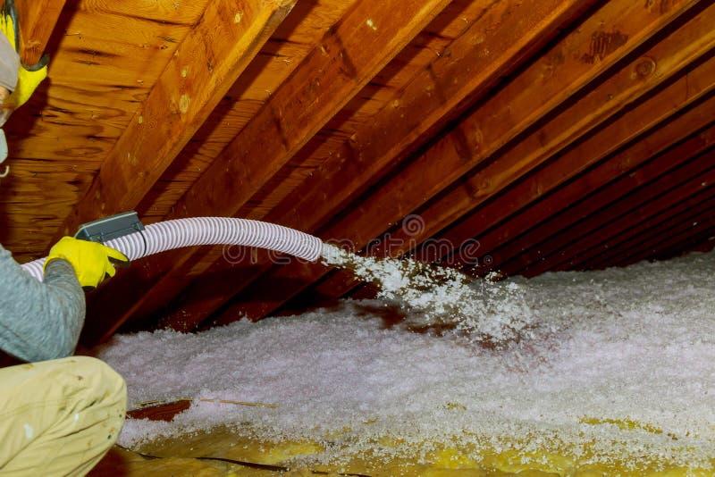 Der Techniker, der durchgebrannte Fiberglas-Isolierung zwischen Dachboden sprüht, bündelt Schaumisolierungs-Bauschaum vom Gewehr  stockbild