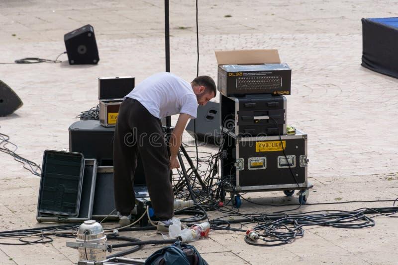 Der Techniker schlie?t die Musikkabel und die Sprecher drau?en an stockbild