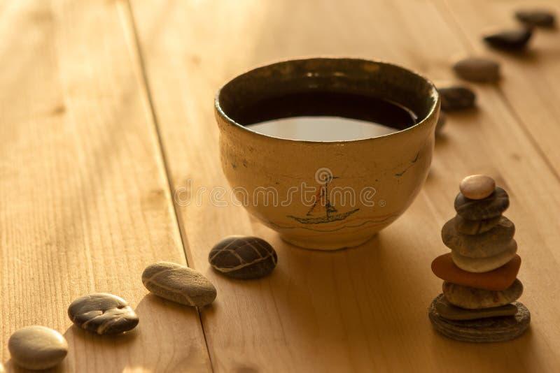 Der Tee in eine Schüssel auf hölzernen Brettern stockfotos