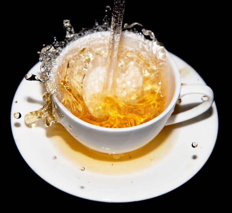 Der Tee, der in eine Untertasse mit ausgelaufen wird, spritzt auf einem schwarzen Hintergrund stockfotografie