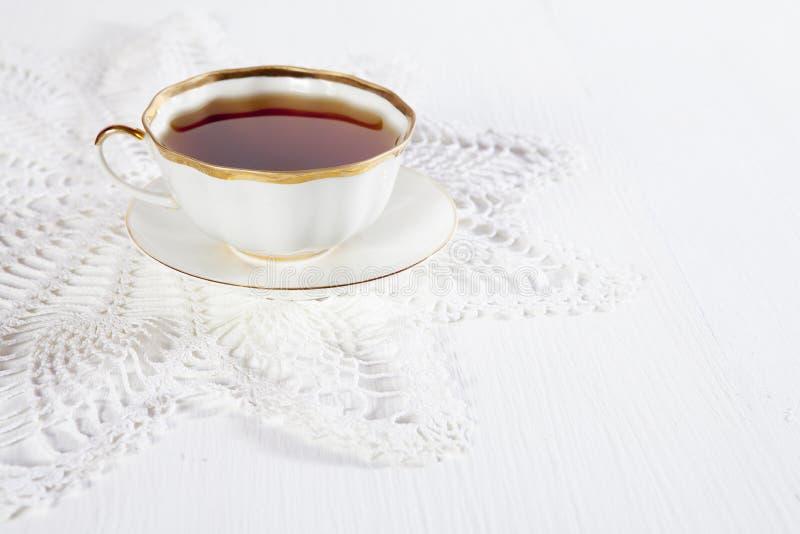 Der Tee in einer weißen Schale auf einer Spitzen- Serviette auf einem weißen Holztisch Kopieren Sie Platz lizenzfreie stockfotos