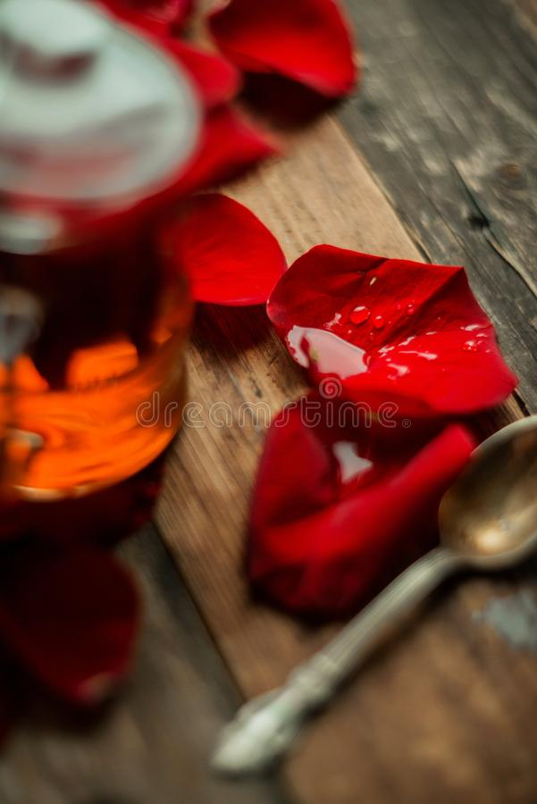 Der Tee, der von den rosafarbenen Blumenblättern des Tees in einer Glasschüssel auf hölzernem rustikalem Hintergrund gemacht wurd lizenzfreie stockfotos