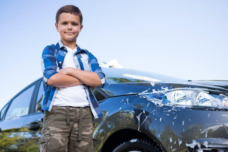 Der Teenager, der mit den Armen steht, kreuzte nahe einem Auto stockbild