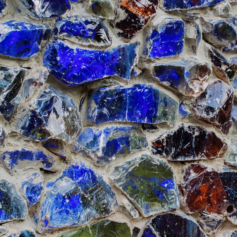Der Teil der rauen Wände schließen oben verziert mit farbigen blauen Steinen, Beschaffenheitshintergrund stockfoto