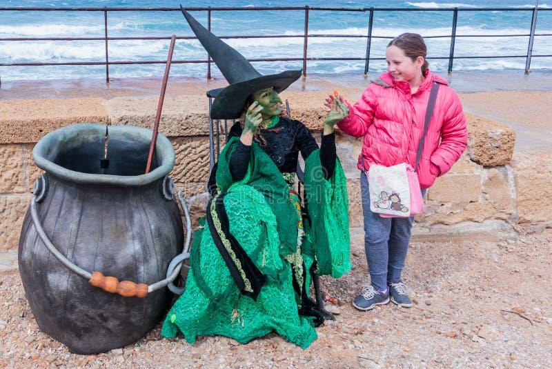 Der Teilnehmer des Festivals gekleidet als Hexe gibt die Mädchensüßigkeit lizenzfreies stockfoto
