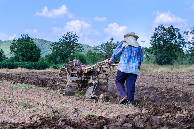 Der thailändische Landwirt, der Einachsschlepper für bebauten Boden für verwendet, bereiten Plantage vor stockbild