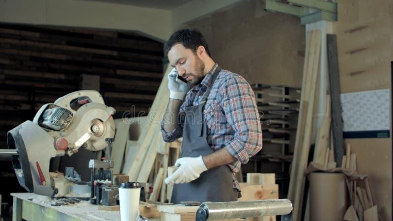 Der Tischler, der an seinem Handwerk in einer staubigen Werkstatt arbeitet und sprechen Telefon lizenzfreie stockfotos