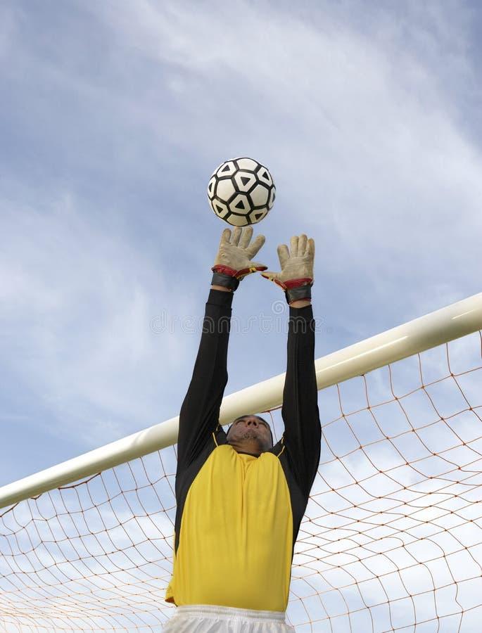 Der Torhüter springend, um den Ball zu fangen stockfoto