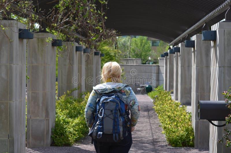 Der Tourist der jungen Frau, der einen Rucksack trägt, wandert durch die botanischen Gärten US und erforscht die Blumen stockbilder