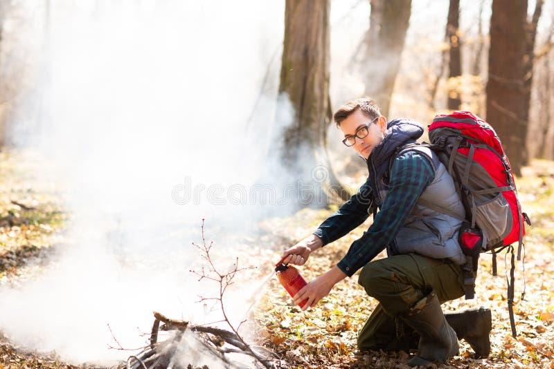 Der Tourist l?scht das Feuer vom Feuerl?scher, nach einem Rest in der Natur stockbilder