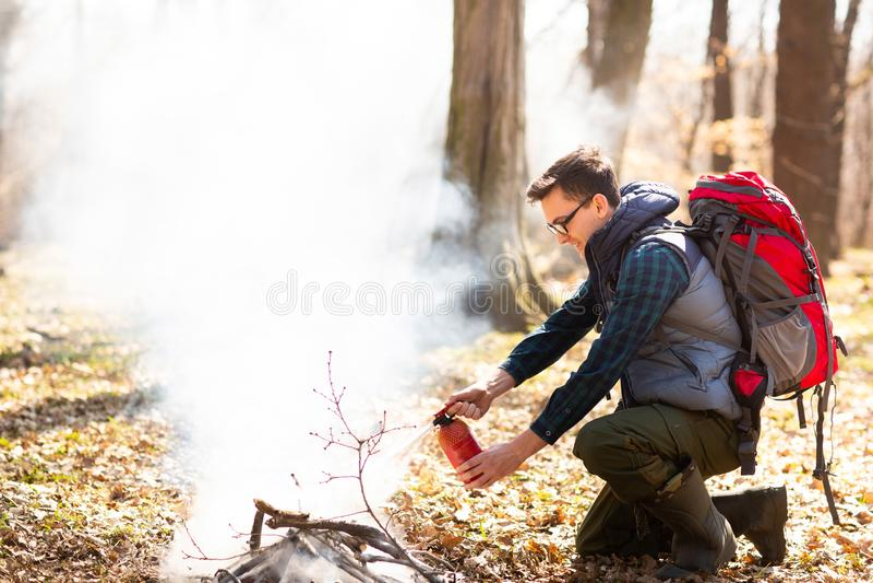 Der Tourist l?scht das Feuer vom Feuerl?scher, nach einem Rest in der Natur stockfotografie