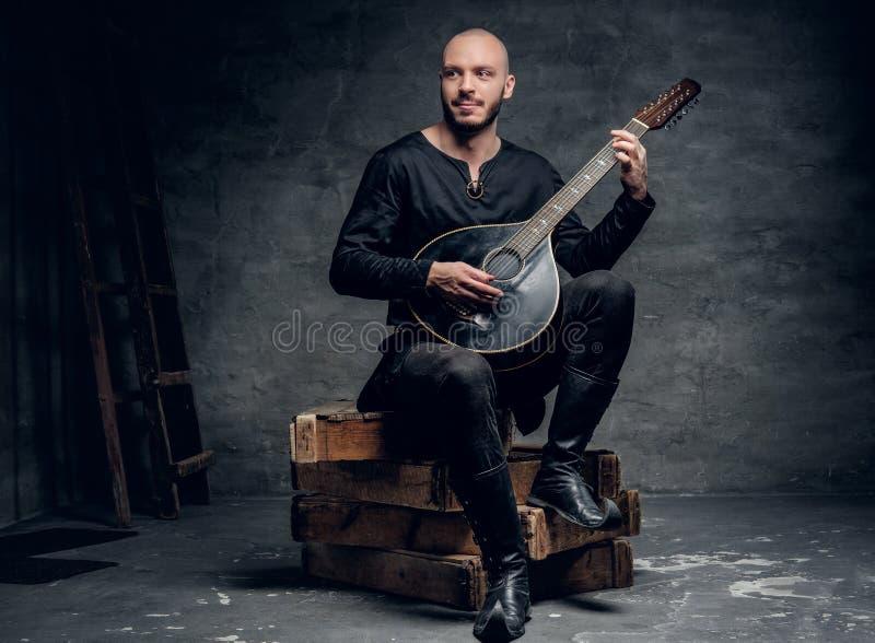 Der traditionelle Volksmusiker, der in der keltischen Kleidung der Weinlese gekleidet wird, sitzt auf einer Holzkiste und spielt  stockbilder