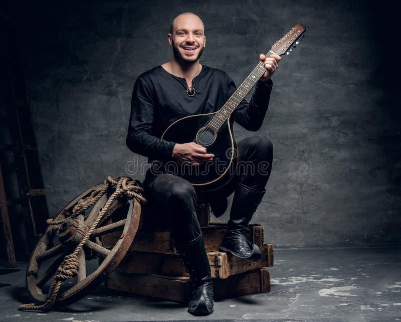 Der traditionelle Volksmusiker, der in der keltischen Kleidung der Weinlese gekleidet wird, sitzt auf einer Holzkiste und spielt  lizenzfreie stockbilder