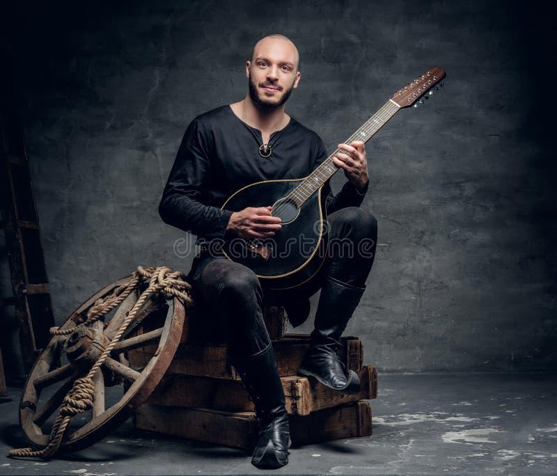 Der traditionelle Volksmusiker, der in der keltischen Kleidung der Weinlese gekleidet wird, sitzt auf einer Holzkiste und spielt  stockbild
