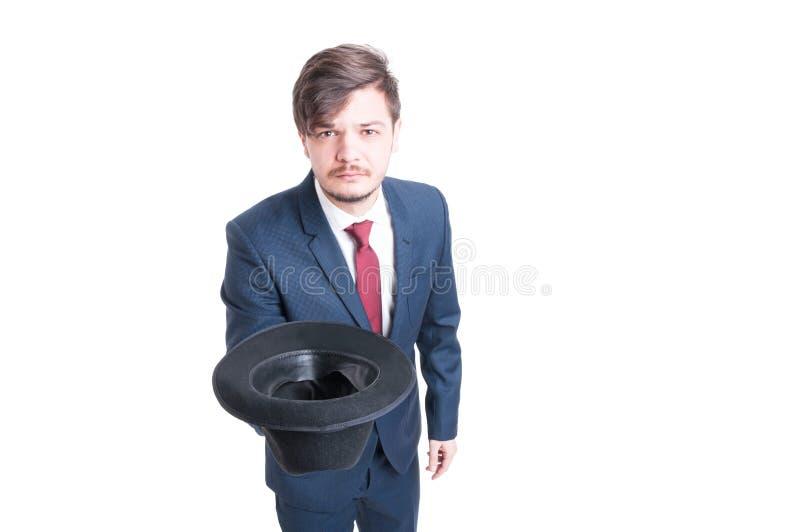 Der tragende Anzug des jungen Mannes, der Hut hält, mögen bitten lizenzfreie stockbilder