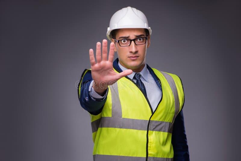 Der tragende Schutzhelm des Mannes und die Bauweste lizenzfreies stockfoto