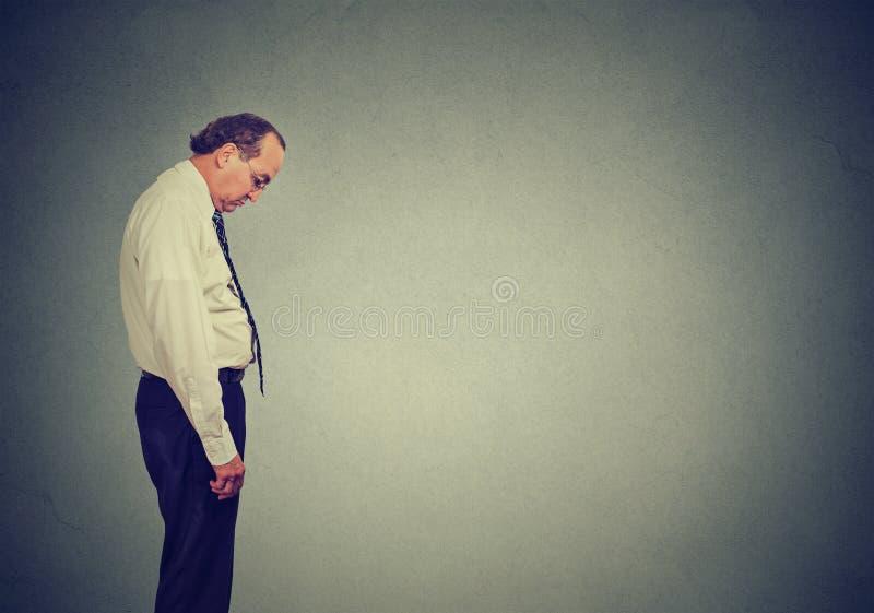 Der traurige einsame Geschäftsmann, der unten schaut, hat keine Energiemotivation im niedergedrückten Leben stockfotografie