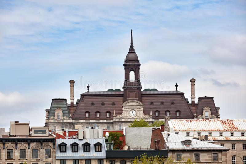 Der Turm, die Uhr und das Dach des Montreal-Rathauses hotel de Ville gegen hellen bewölkten Himmel in altem Montreal, Quebec, Kan lizenzfreie stockfotos