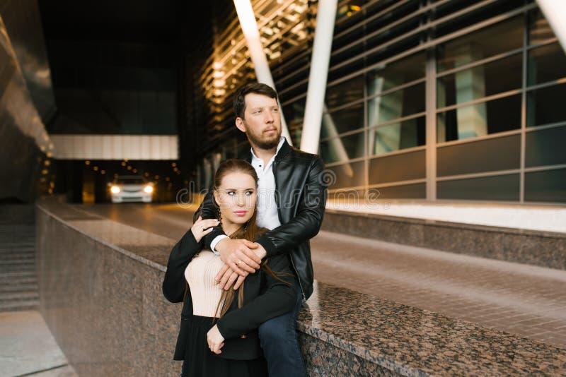 Der Typ umarmt seine Freundin, gefolgt von einem Auto in der Ferne, bei dem das Licht an Das Paar blickt in die Zukunft Stilvolle stockbilder