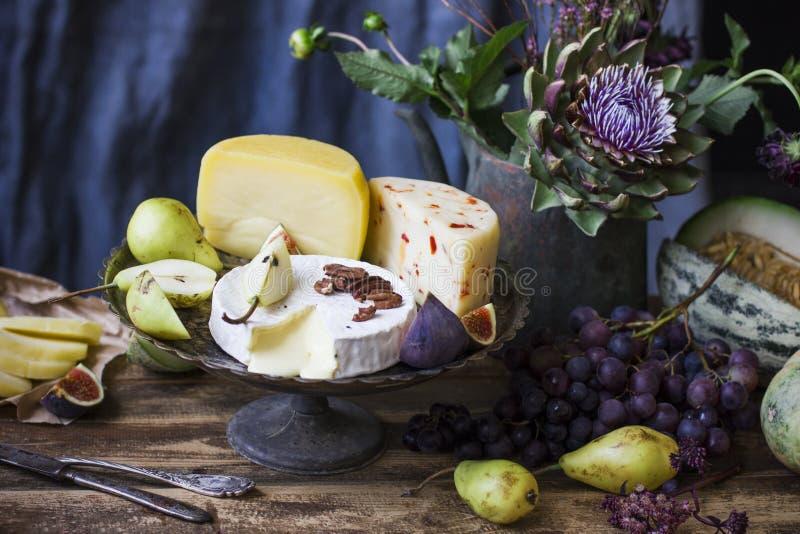 Der unterschiedliche Käse, die frische Frucht und die Gartenblumen auf altem Holz stockbilder