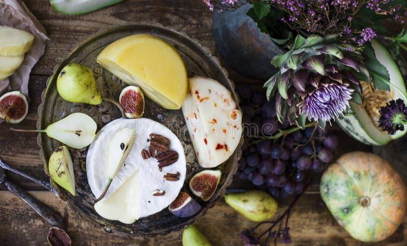 Der unterschiedliche Käse, die frischen Früchte und die Gartenblumen auf hölzernem Hintergrund lizenzfreie stockfotos