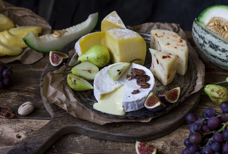 Der unterschiedliche Käse und die frischen Früchte stockbild