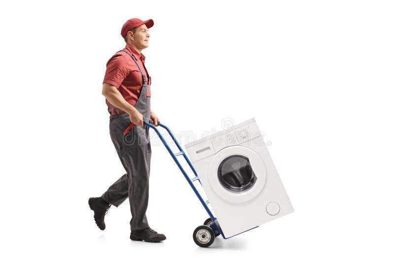 Der Urheber, der einen Hand-LKW drückt, lud mit einer Waschmaschine stockbilder