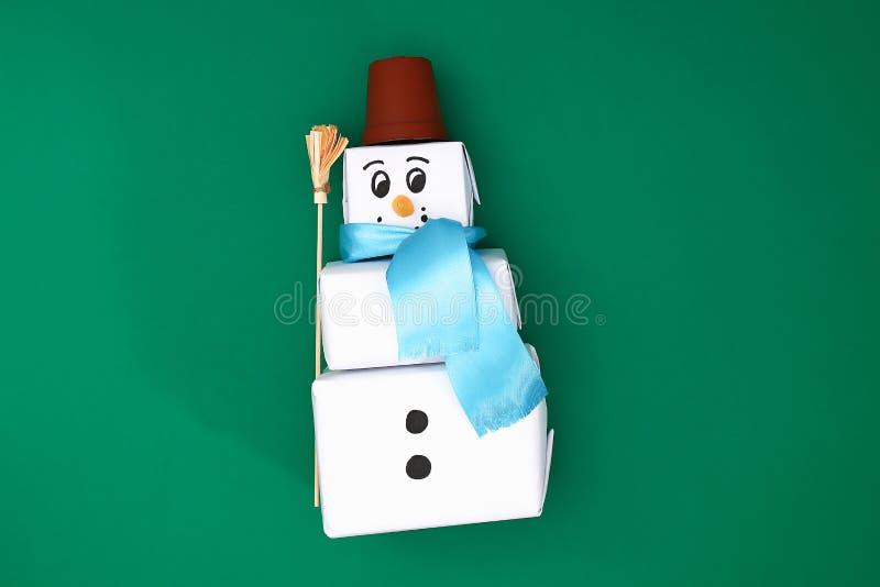 Der ursprüngliche Entwurf des Geschenks des Weihnachten drei des Weißbuches, ein Satinband in Form eines Schneemannes auf einem g lizenzfreie stockbilder