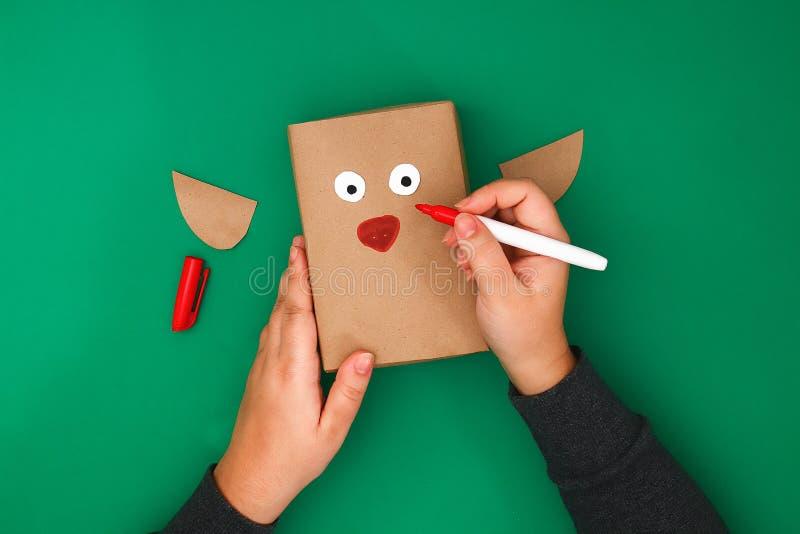 Der ursprüngliche Entwurf eines Weihnachtsgeschenks vom Kraftpapier in Form eines Rotwilds auf einem grünen Hintergrund Schritt f stockfoto