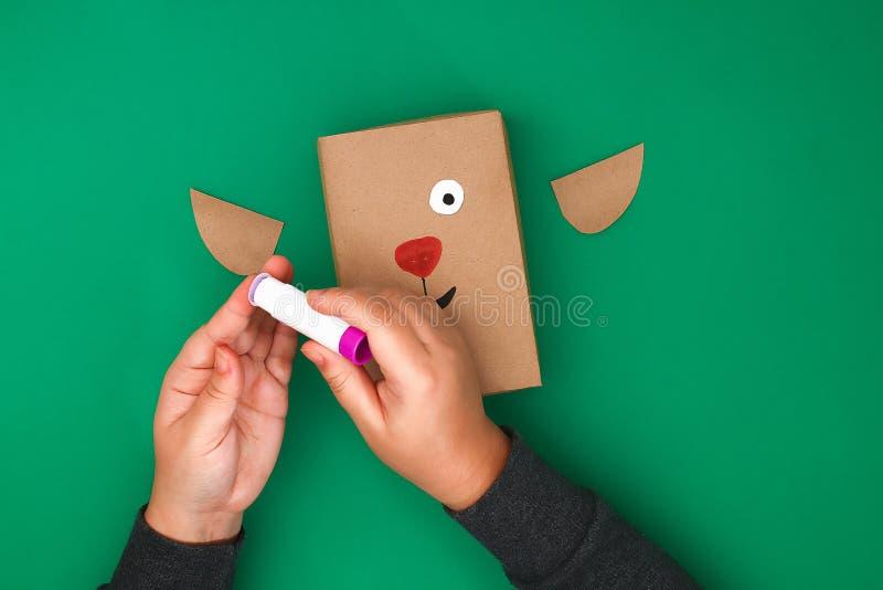 Der ursprüngliche Entwurf eines Weihnachtsgeschenks vom Kraftpapier in Form eines Rotwilds auf einem grünen Hintergrund Schritt f lizenzfreie stockfotos