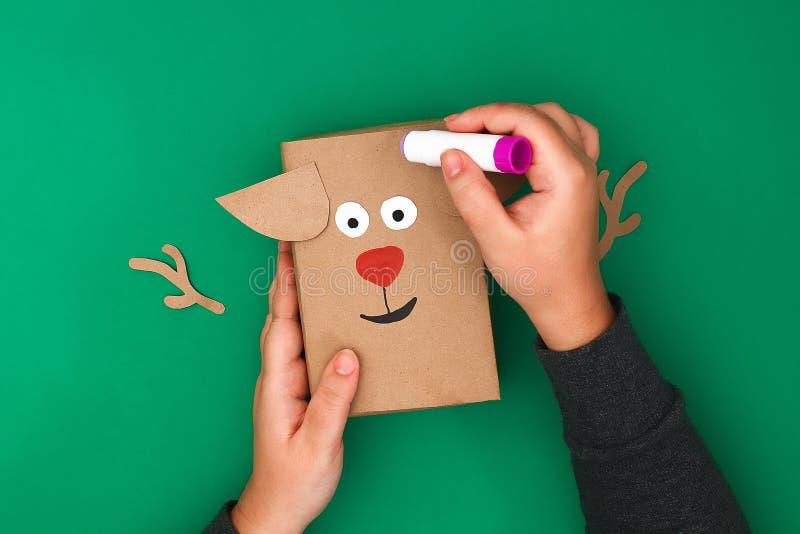 Der ursprüngliche Entwurf eines Weihnachtsgeschenks vom Kraftpapier in Form eines Rotwilds auf einem grünen Hintergrund Schritt f lizenzfreies stockfoto
