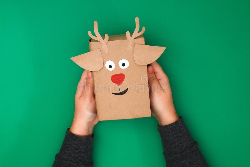 Der ursprüngliche Entwurf eines Weihnachtsgeschenks vom Kraftpapier in Form eines Rotwilds auf einem grünen Hintergrund Schritt f stockbilder