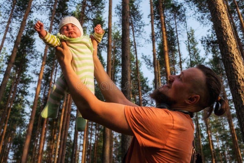Der Vater, der mit seinem netten kleinen Sohn im Wald ist er spielt, bewegliches Baby in seinen otstretched Armen, die zum Himmel lizenzfreies stockfoto