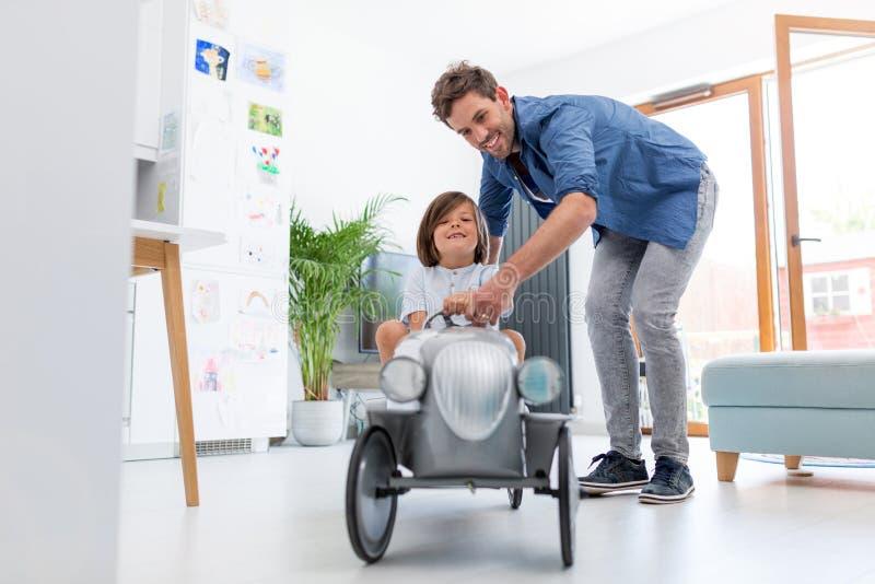 Der Vater, der seinem Sohn hilft, ein Spielzeug zu fahren, bieten Auto feil stockfotografie
