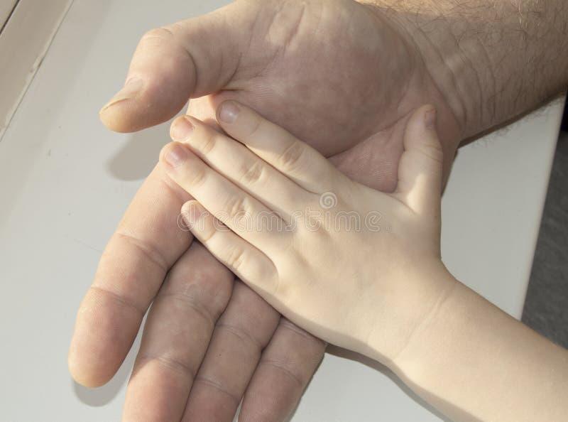 Der Vater, der sorgfältig in seiner Hand die Hand eines Kindes hält Glückliche Familie, Sorgfalt und Liebe, der Vatertag stockbilder