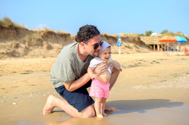 Der Vater und Baby, die am Seeufer neugeboren sind, setzen in der Sommerfamilie auf den Strand lizenzfreie stockfotografie