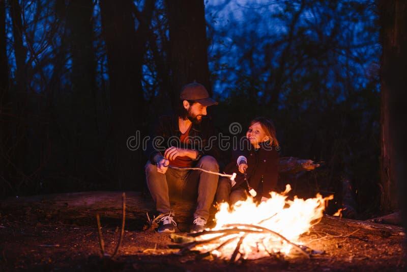 Der Vater und sein Sohn, die auf sitzen, meldet den Wald vor einem Feuer und Brateibische auf den Zweigen an lizenzfreies stockfoto