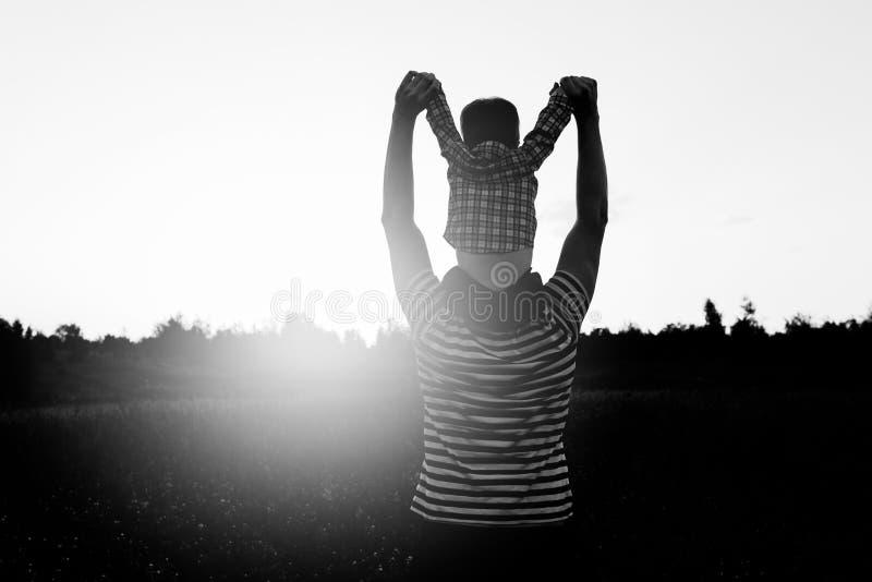 Der Vater und Sohn, die auf das Feld zur Sonnenuntergangzeit, der Junge an sitzt geht, bemannt Schultern Konzept der freundlichen lizenzfreies stockbild